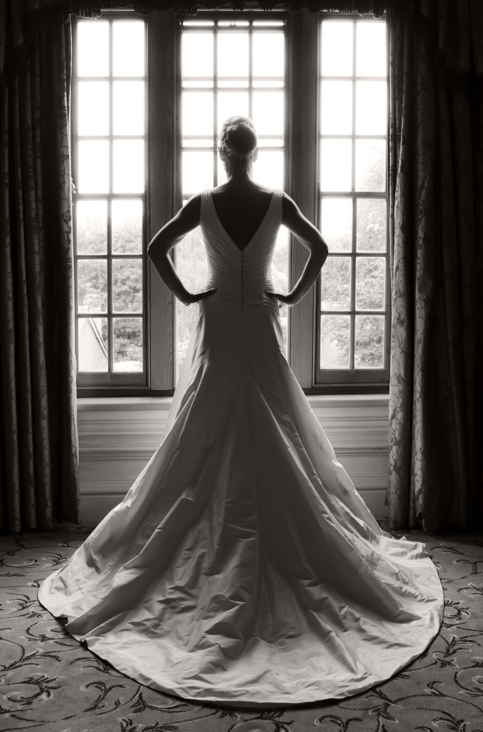 bride standing in front of a window looking out