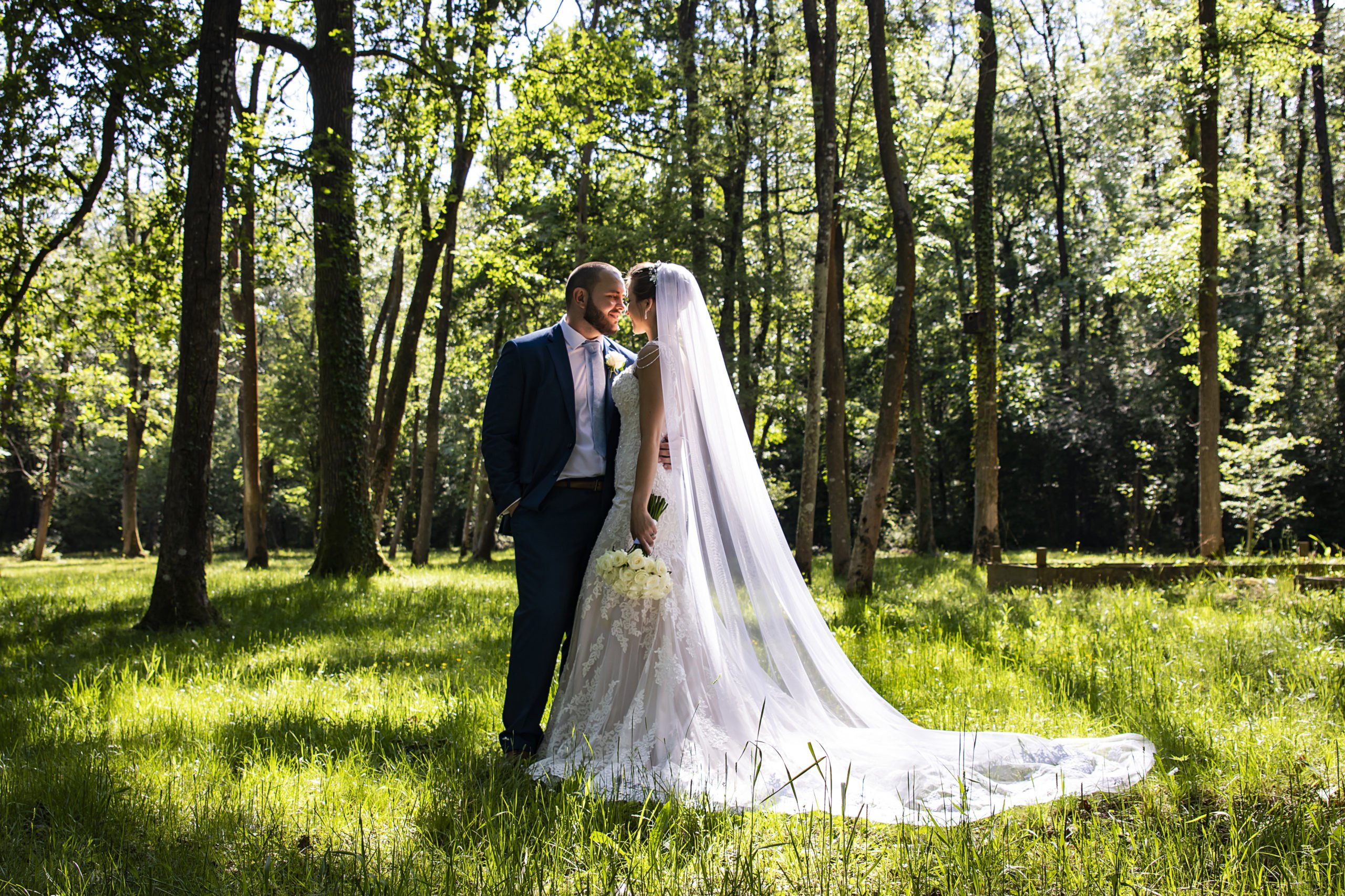 couple standing together in a forest clearing on a sunny day
