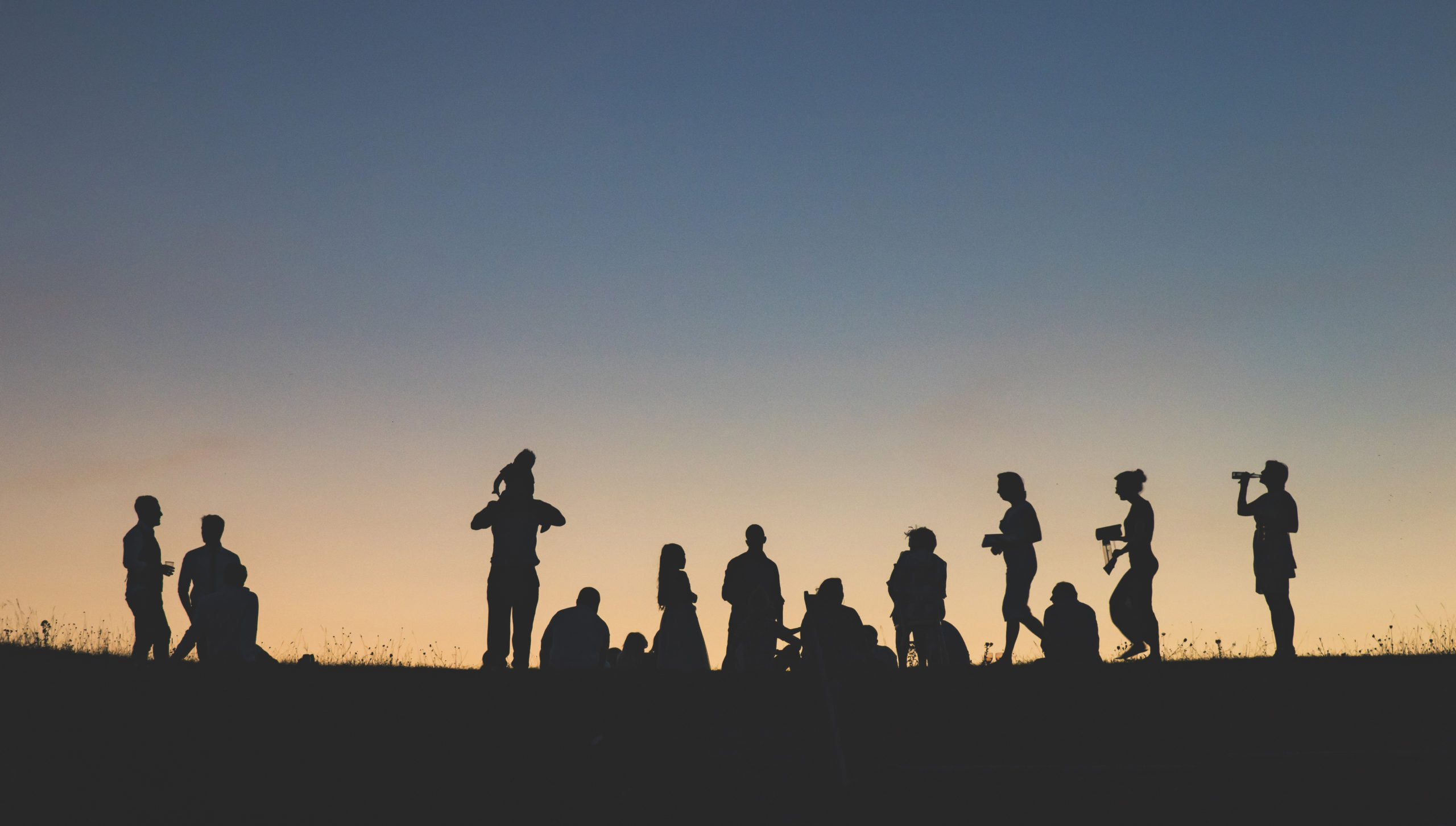 group of people standing on hill silhouette