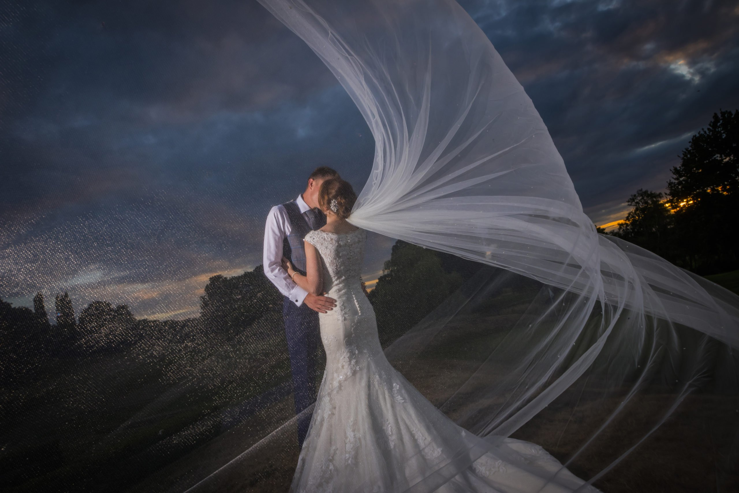 couple kissing outside at night with veil blowing