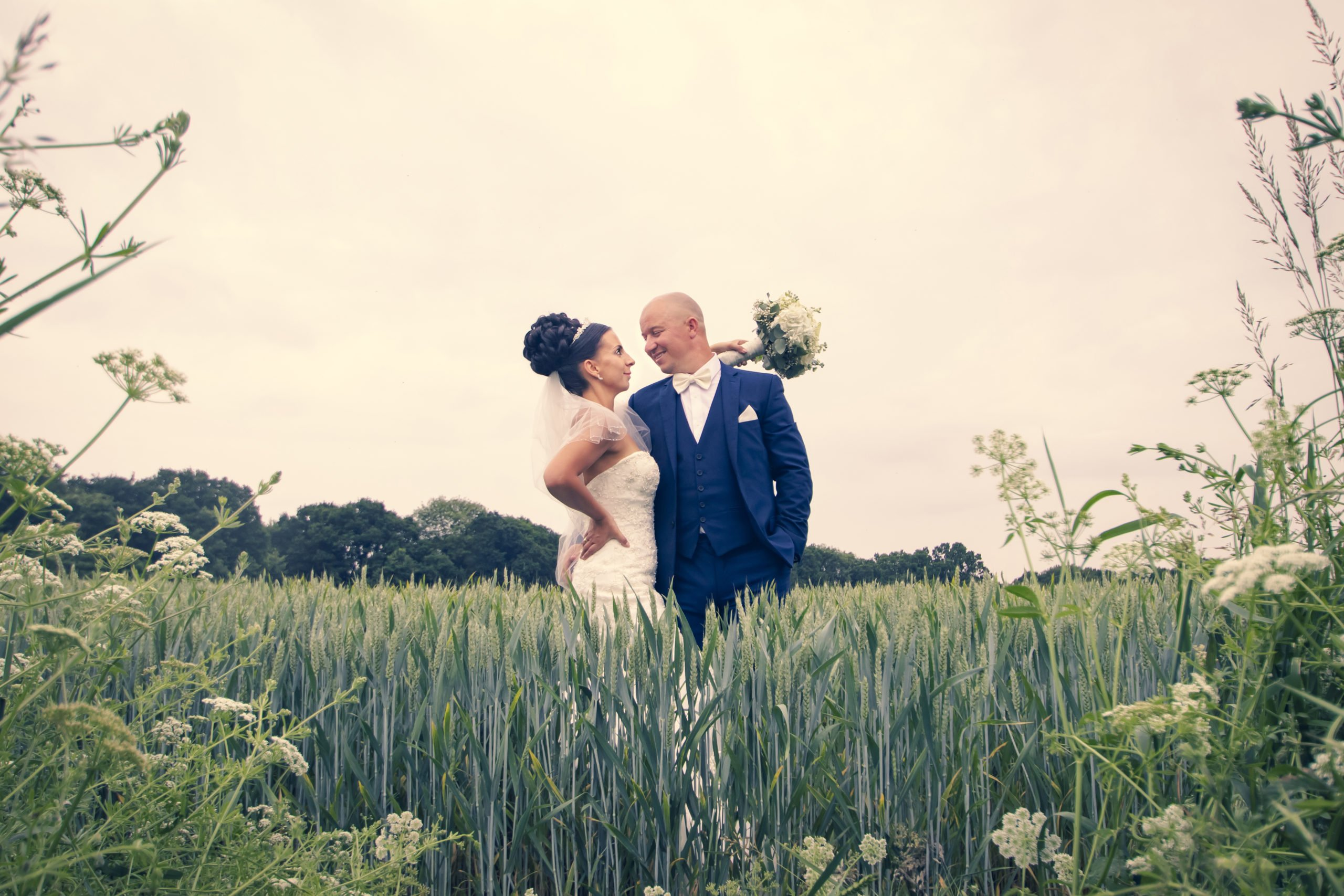 couple standing together in green cornfield