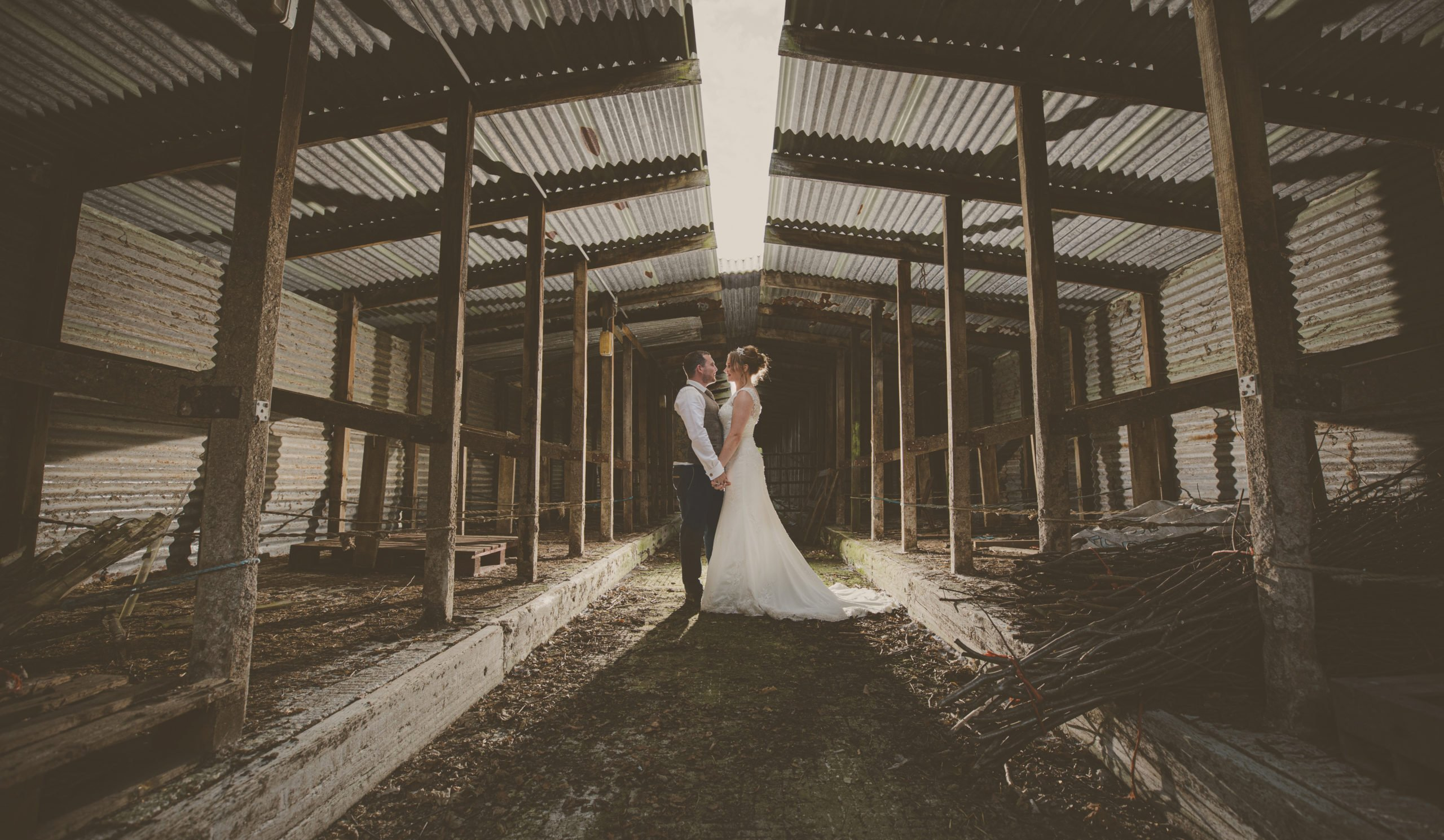 couple standing together in derelict barn