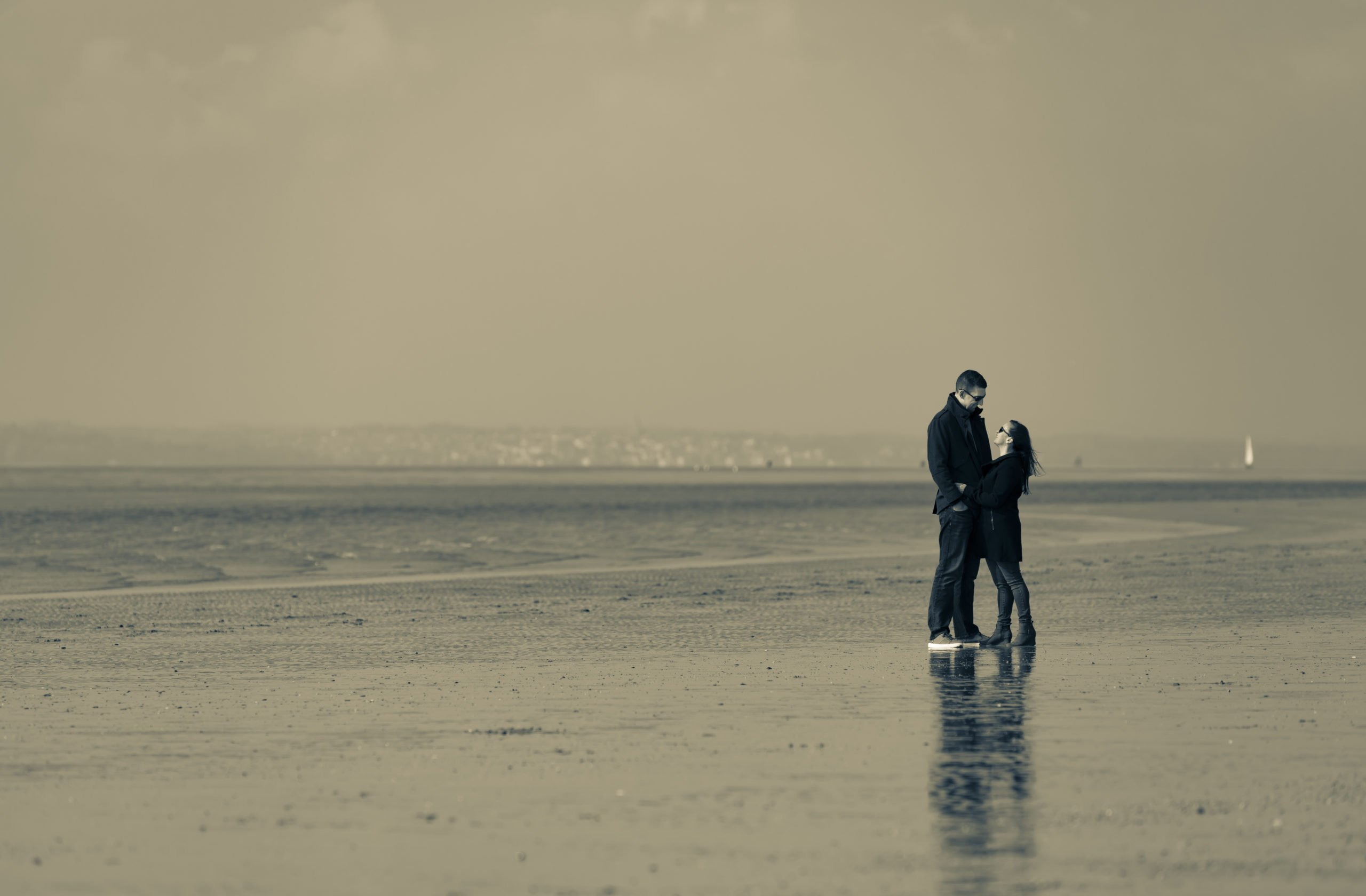 couple standing together on a beach with the tide out